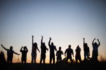 silhouettes of people with raised hands outdoors at dusk
