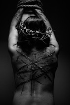 The suffering of Christ -- a beaten Jesus in His crown of thorns bound to the cross with rope.