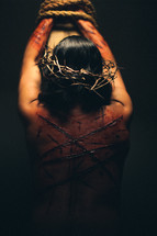 The suffering of Christ -- a beaten and scarred Jesus in His crown of thorns, bound to the cross with ropes.
