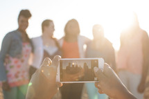 woman taking a picture of a group of women with her cellphone