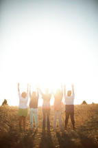 women with raised hands outdoors at sunset