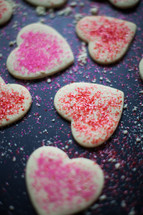 pink and red sprinkles on heart shaped cookies