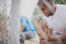 man praying in a baseball dugout