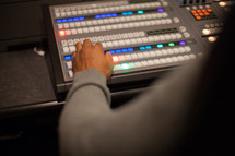 hands on a control panel for a sound system
