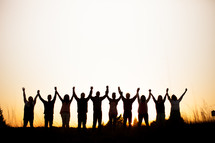 silhouette of a row of people with raised hands in praise outdoors