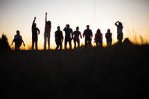 raised hands, praise, man, woman, silhouettes, group, people, row, standing, field, outdoors, worship
