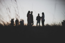 silhouettes of a group of people standing in a field