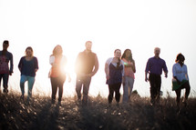 group of people walking outdoors in a field at sunset
