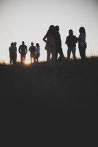 groups gathering outdoors talking at sunset