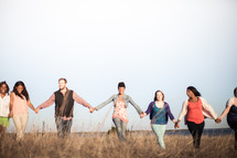 group holding hands in fellowship outdoors
