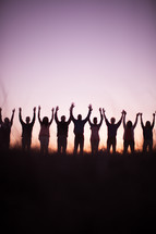 silhouette of people in a row outdoors with raised hands in praise