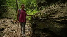 a woman with a walking stick hiking on a trail