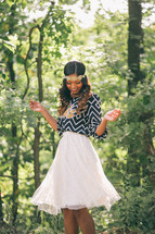 An African-American woman standing in a forest twirling in a skirt