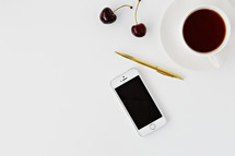 iPhone, gold pen, cherries, and coffee on white