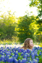 little girl lying in a field of blue bonnet flowers
