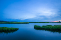 Blue tinted sunset reflection with marsh grass waterway on the coast
