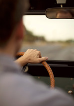Man with hand hand on steering wheel