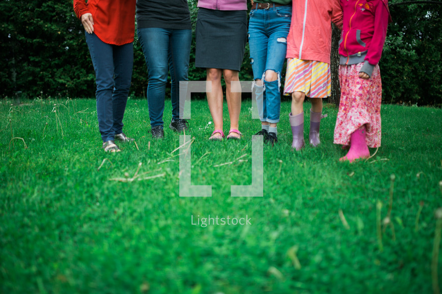 legs of females standing outdoors in grass