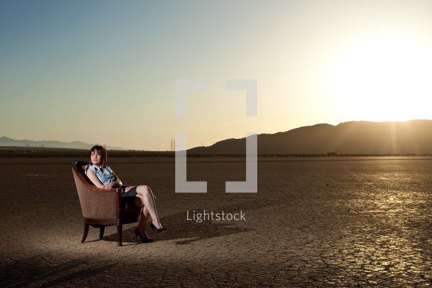 woman sitting in a chair on parched earth
