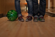 Two pairs of legs in jeans  and bowling shoes standing on wood floor with green bowling ball.