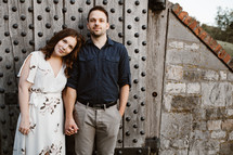 a couple standing in front of a shed
