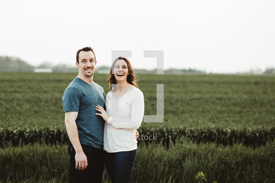 a couple holding each other in a field