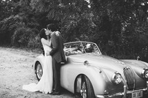 bride and groom kissing in front of an old car