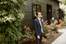 groom standing outdoors in front of a house