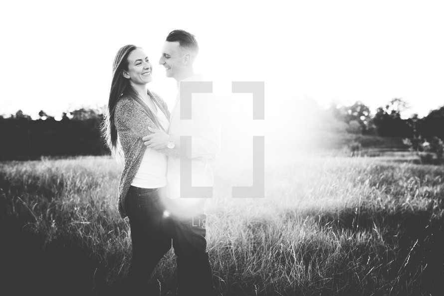 a couple standing together hugging in a field
