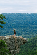 woman standing with raised arms on a mountaintop