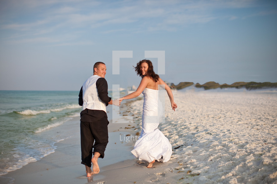 bride and groom holding hands and running on a beach