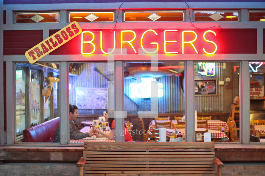 couple holding hands inside a Burger joint