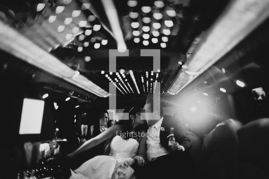 bride and groom kissing in the back of a limo