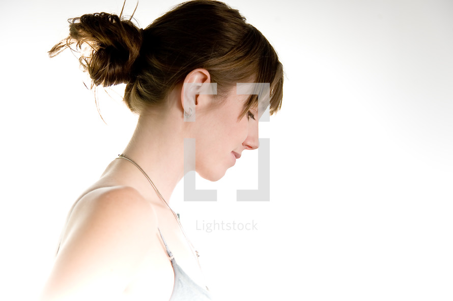profile of a woman with her hair up looking down