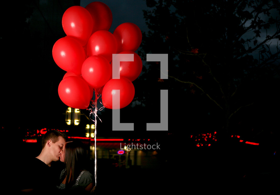 man and woman kissing under red balloons