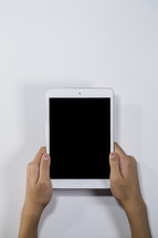hands holding up an iPad