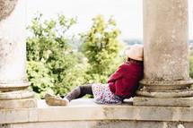 a little girl resting outdoors between columns