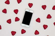 red heart shaped chocolates and cellphone