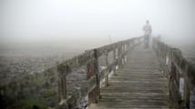 man walking over a boardwalk on a foggy morning