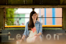 young woman sitting on a bench with coffee