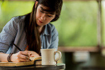 young woman reading a Bible and journaling