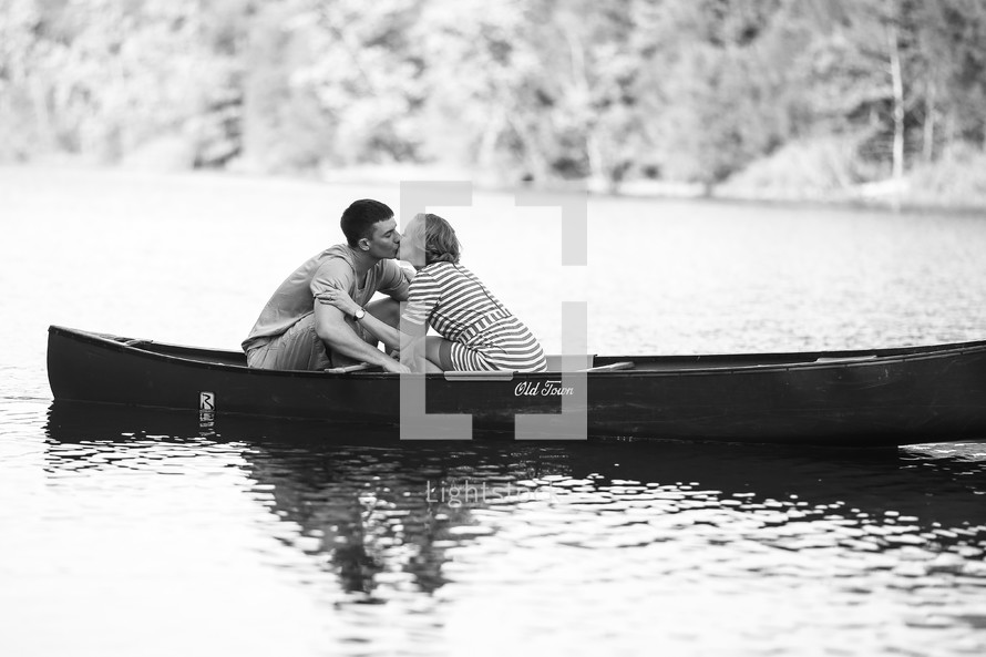 A couple kissing in a canoe