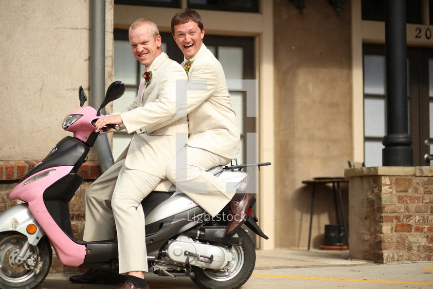 groomsmen riding on a pink motorized scooter
