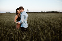 a couple snuggling in a field