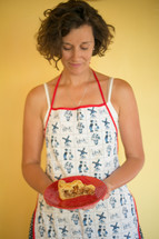 woman in an apron holding a slice of pie