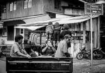 people riding in the back of a truck in Toraja