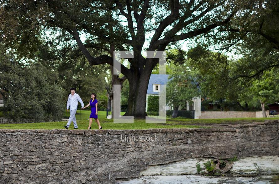 couple walking hand in hand on a neighborhood sidewalk