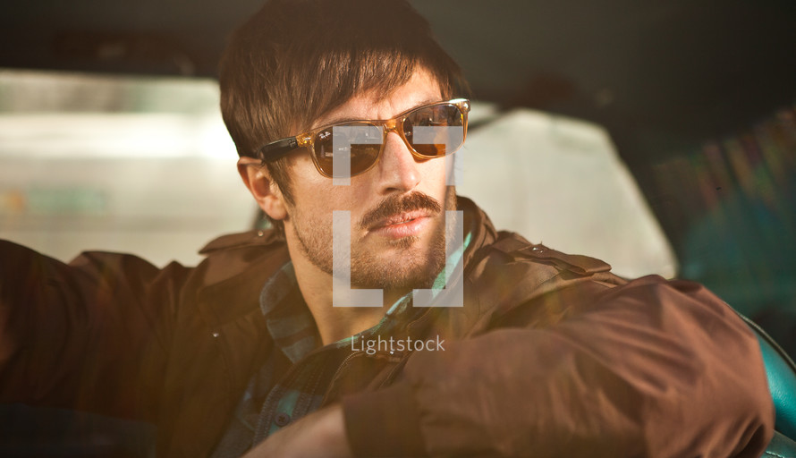man looking out a car window wearing sunglasses