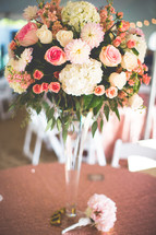 a centerpiece of flowers in a tall vase at a wedding reception