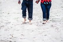a couple walking through sand holding hands
